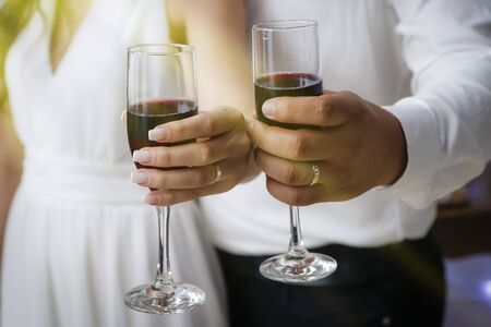hands detail with wedding rings and wine glasses - grooms toast - golden wedding rings