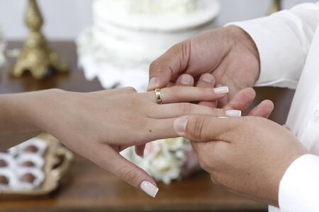 hands together exchanging wedding rings - Grooms hands joined using wedding rings - golden wedding rings