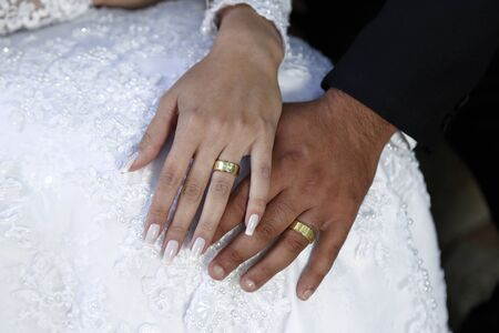 United hands and wedding rings, detail of hands of bride and groom wearing wedding rings, wedding rings, jewelry, joined hands.