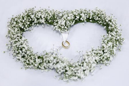 Heart shaped white flower arrangement with wedding rings tied in green ribbon
