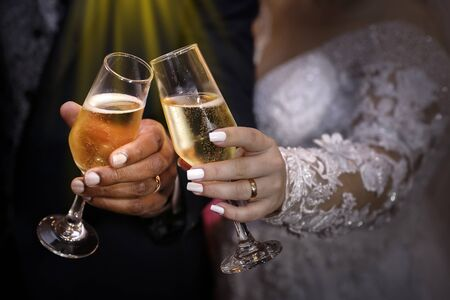 hand detail with wedding rings and champagne glasses - grooms toast - golden wedding rings