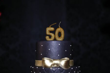 black birthday cake candle detail with golden details - fiftieth birthday - 50th candle.