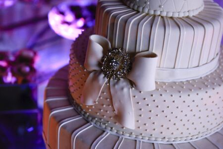detail of shaded white wedding cake at reception