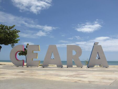 arriving signage tourism board with Ceara inscription in large, colorful letters on the beach and sea in the city of Fortaleza, state of Ceara, Brazil