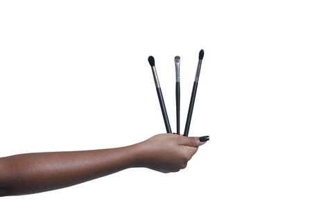 Female hand holding three makeup brushes Banco de Imagens - 147744485
