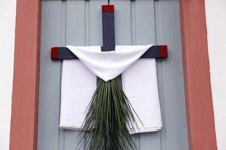 cross arrangement with branches, leaves and fabric on the wall during the Catholic celebration of Palm Sunday Banco de Imagens - 148286703