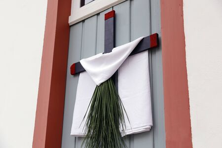 cross arrangement with branches, leaves and fabric on the wall during the Catholic celebration of Palm Sunday