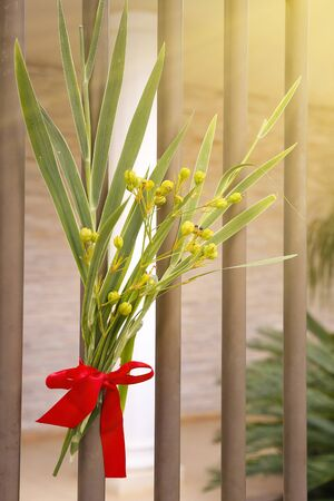 arrangement with branches and fabric lace on gate during Catholic Palm Sunday celebration