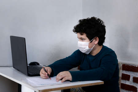 white young boy improvises study with computer and wearing respiratory protection mask