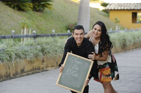 portrait of beautiful young wedding couple posing at outdoor photo shoot holding Save the date sign Banco de Imagens