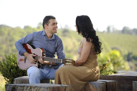 portrait of beautiful young wedding couple posing in outdoor photoshoot playing guitar