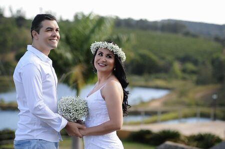 portrait of beautiful young wedding couple posing in outdoor photoshoot with white clothes and flowers Banco de Imagens