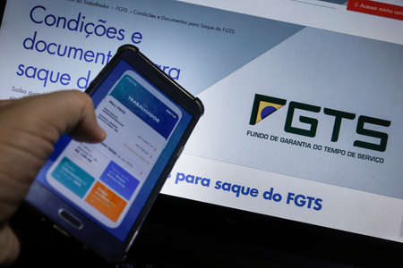 Minas Gerais / Brazil - June 15, 2020: computer screen and cell phone with Caixa bank FGTS application for emergency financial withdrawal. Editorial