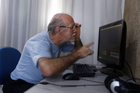 senior adult man working from home using computer, home office system Banco de Imagens