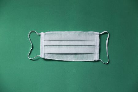 White protective facial respiratory mask on green background