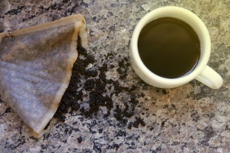 table with coffee grounds in the strainer and white cup with coffee