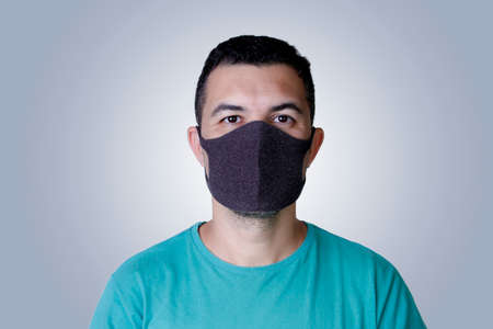 portrait handsome young adult white man wearing dark protection mask Imagens