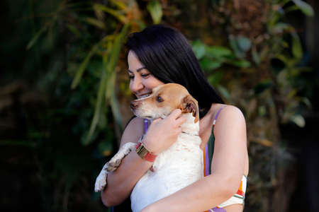 Adult brunette white woman playing with her dog pet