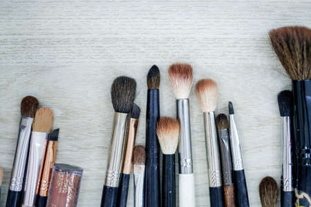 various brushes for production and misaligned makeup on wooden surface
