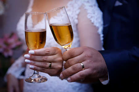 detail hands of wedding couple wearing golden wedding rings and glass bowl containing alcohol drink