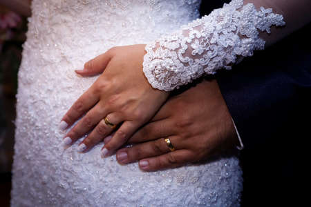 detail of hands of newlyweds at wedding displaying gold wedding rings Imagens