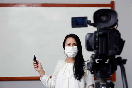 Teacher with respiratory protection mask during presentation of online virtual class Imagens