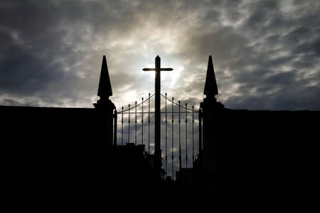 front view of cemetery in backlight, with gate, cross, stonework; towers and cloudy sky Imagens