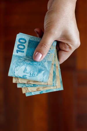 Hands holding Brazilian real notes, money from Brazil, notes of Real, Brazil BRL banknote, Brazilian currency, economy and business.