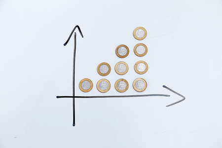 coins on white background and directional arrows indicating growth of time and profits - finance, income and interest concept.