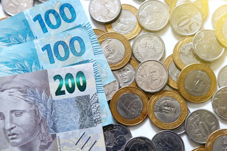 money banknotes and group of brazilian real coins - economy and finance concept Banco de Imagens