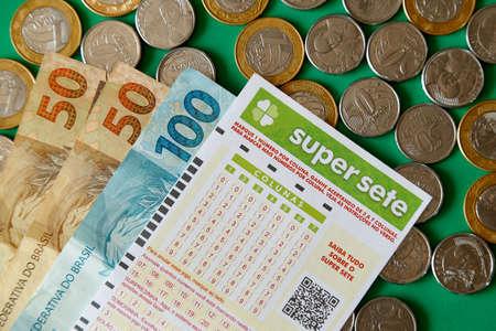 Minas Gerais, Brazil - February 22, 2021: cash notes, coins and lottery ticket Caixa Super Sete