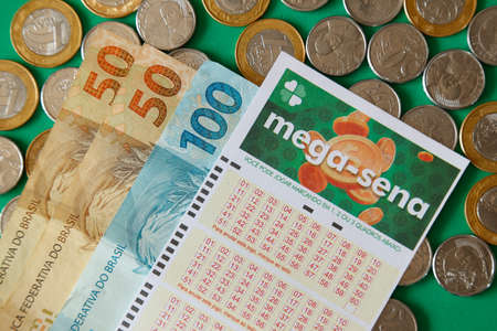Minas Gerais, Brazil - February 22, 2021: cash notes, coins and lottery ticket Caixa Mega Sena Editorial