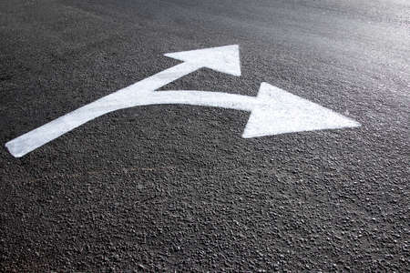 white directional arrow drawn on the asphalt ground - concept of paths and directions