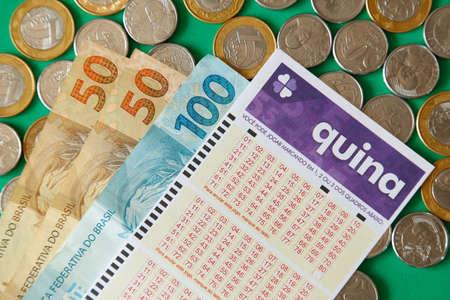 Minas Gerais, Brazil - February 22, 2021: cash notes, coins and lottery ticket Caixa Quina Editorial