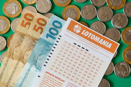 Minas Gerais, Brazil - February 22, 2021: cash notes, coins and lottery ticket Caixa Lotomania