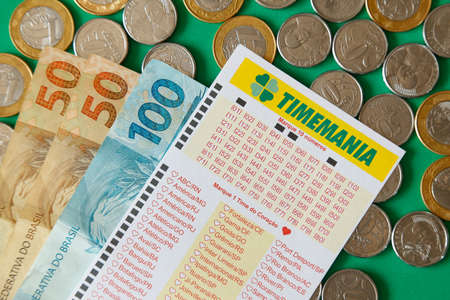 Minas Gerais, Brazil - February 22, 2021: cash notes, coins and lottery ticket Caixa Timemania