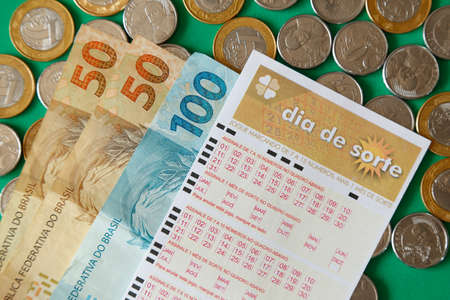 Minas Gerais, Brazil - February 22, 2021: cash notes, coins and lottery ticket