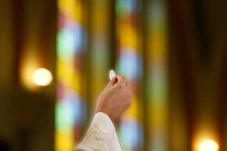 Detail with the priest's hand holding a host at Catholic Mass - Sacred Host