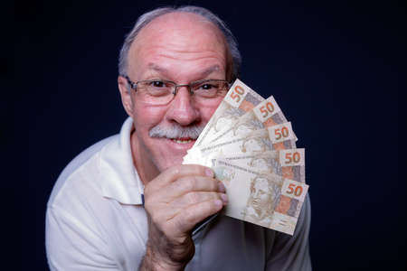 White adult man smiling at camera and holding several Brazilian real money bills Banco de Imagens