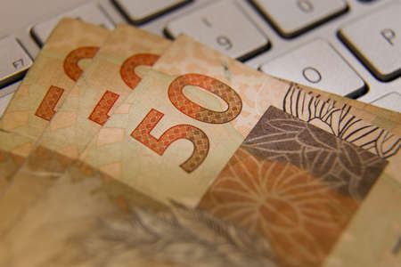 Brazilian real banknotes - Fifty reais banknotes on top of a computer keyboard. BRL in Brazil. Concept of currency, economy and business.