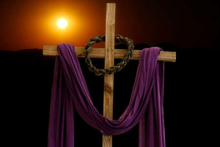 Wooden cross with crown of thorns and purple fabric