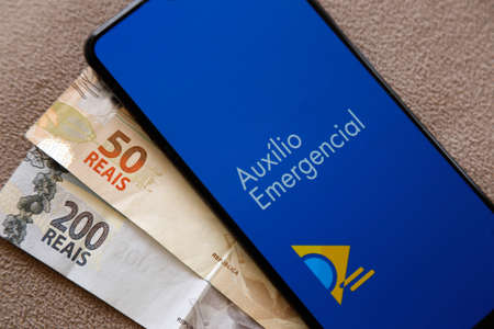 Minas Gerais, Brazil - April 6, 2021: Emergency Aid in mobile phone application and money bills