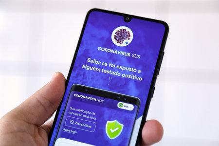 Minas Gerais, Brazil - April 19, 2021: mobile phone screen with Coronavirus SUS do Brasil application Editorial