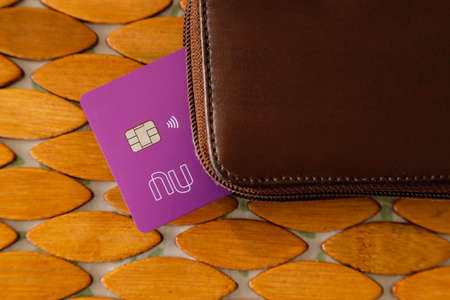 Minas Gerais, Brazil - January 19, 2021: purple credit card with Nubank logo and leather wallet. Form of payment.
