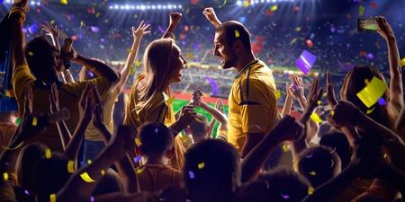deporte: Fans en el juego de fútbol estadio Confeti y oropel