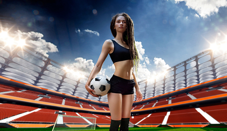 football player: Young sexy woman player in soccer stadium Day