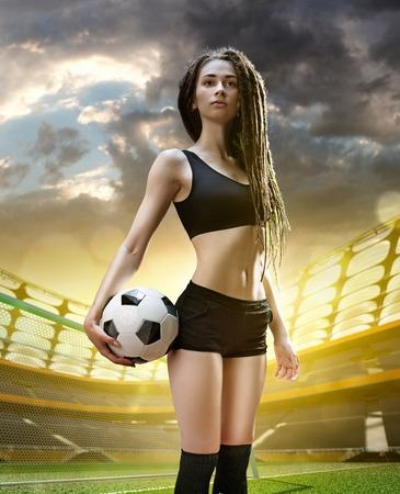 축구 경기장의 날에 젊은 섹시 한 여자 선수