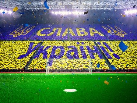 floodlit: Flag Ukraine of fans.Evening stadium arena soccer field championship win. Confetti and tinsel Blue Toning Stock Photo