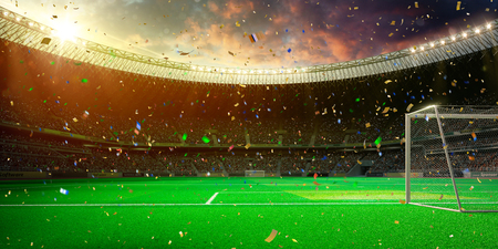 Evening stadium arena soccer field championship win. Confetti and tinsel . Yellow toning 스톡 콘텐츠