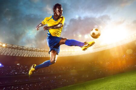 soccer kick: Black soccer player in action. Stadium field evening Stock Photo